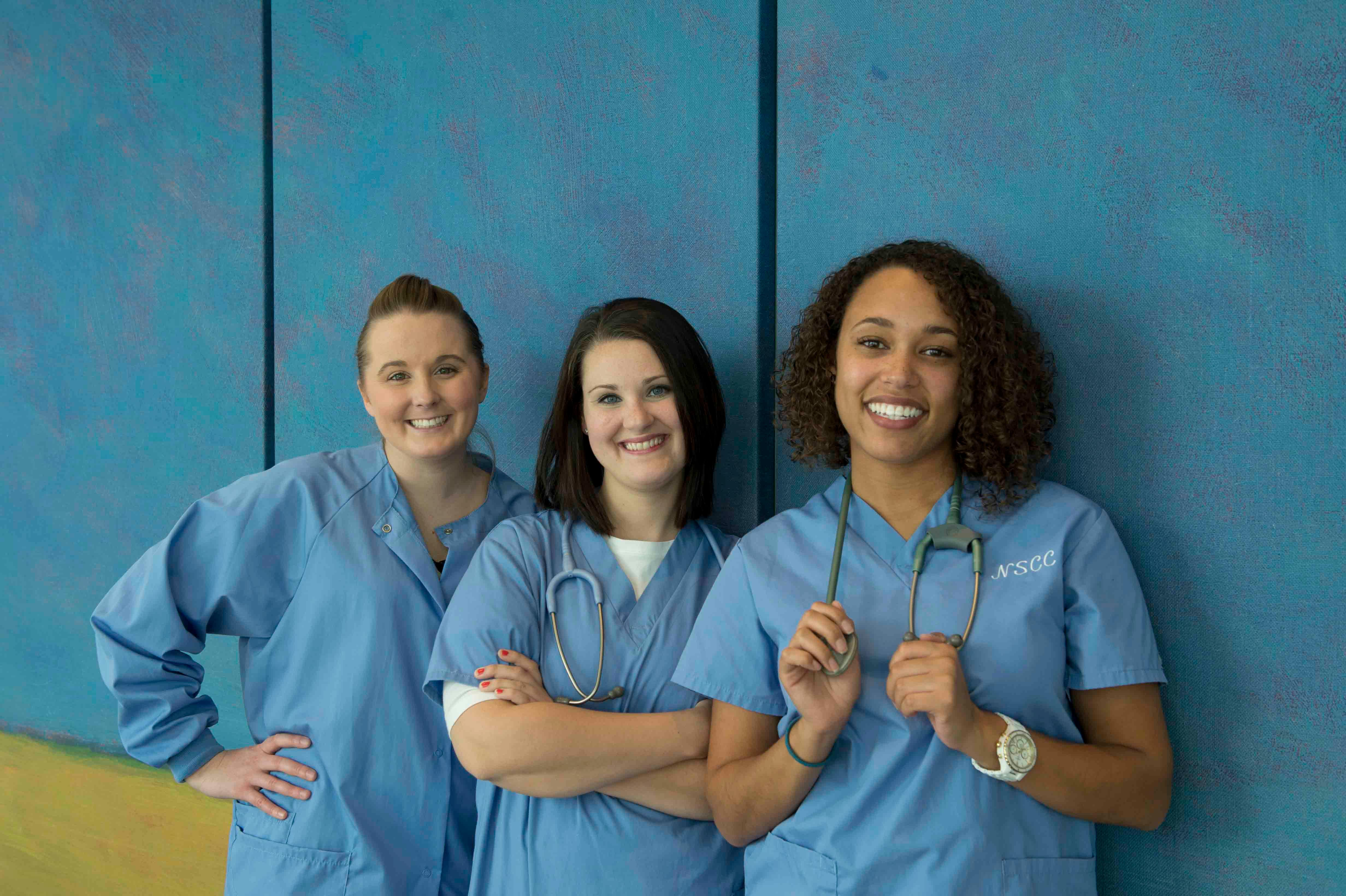 Three nursing students in scrubs
